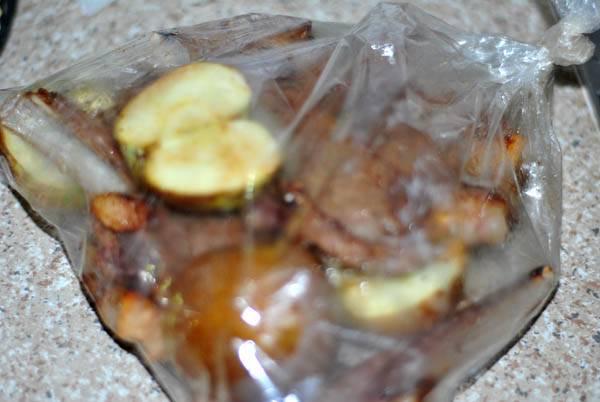 3. Теперь помещаем мясо в пакет для запекания. Сюда же - нарезанные на половинки яблоки. Закрываем края, делаем несколько отверстий сверху, и запекаем 50 минут в разогретой духовке.