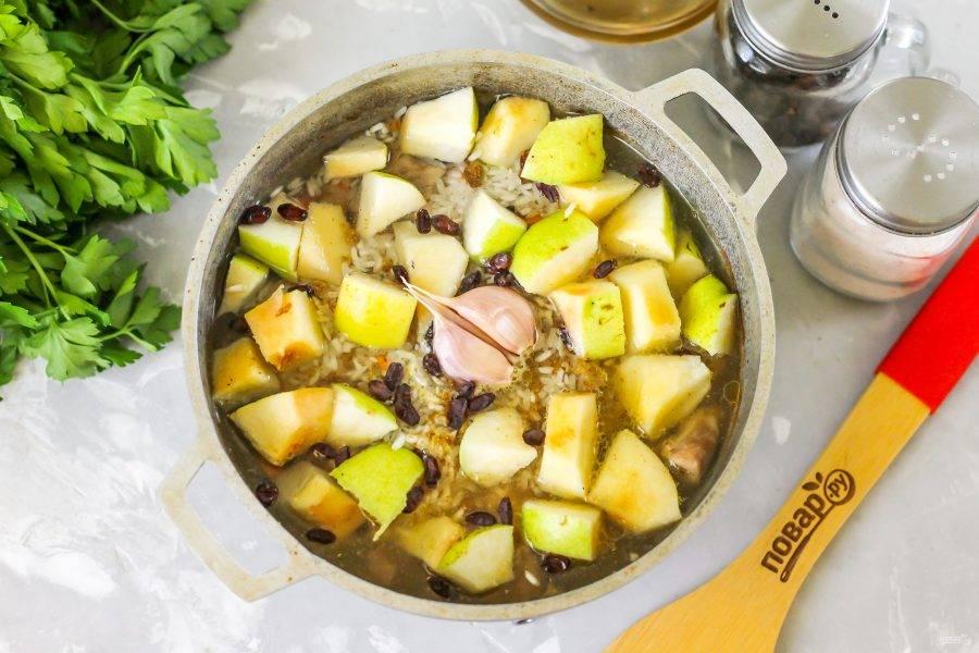 Промойте айву в воде, разрежьте на четыре части и срежьте семена. Мякоть нарежьте кубиками и добавьте с чесноком в казан. Влейте остаток горячей воды, накройте казан крышкой и томите около 25 минут на минимальном нагреве.