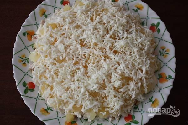 5. Яйца остудите и очистите, отделите белки от желтков. Белки натрите на терке и выложите поверх ананасов.