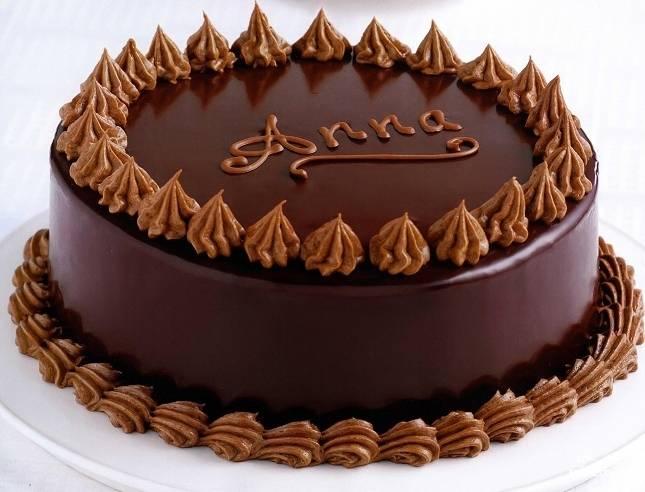 Тортик перекладываем на решетку, даем немного застыть его поверхности. После другую часть ганаша выливаем на корж. Получится плотный шоколадный слой. Тортик убираем в холодильник. Как застынет — украшаем кремом и рисуем надпись Анна. Приятного аппетита!