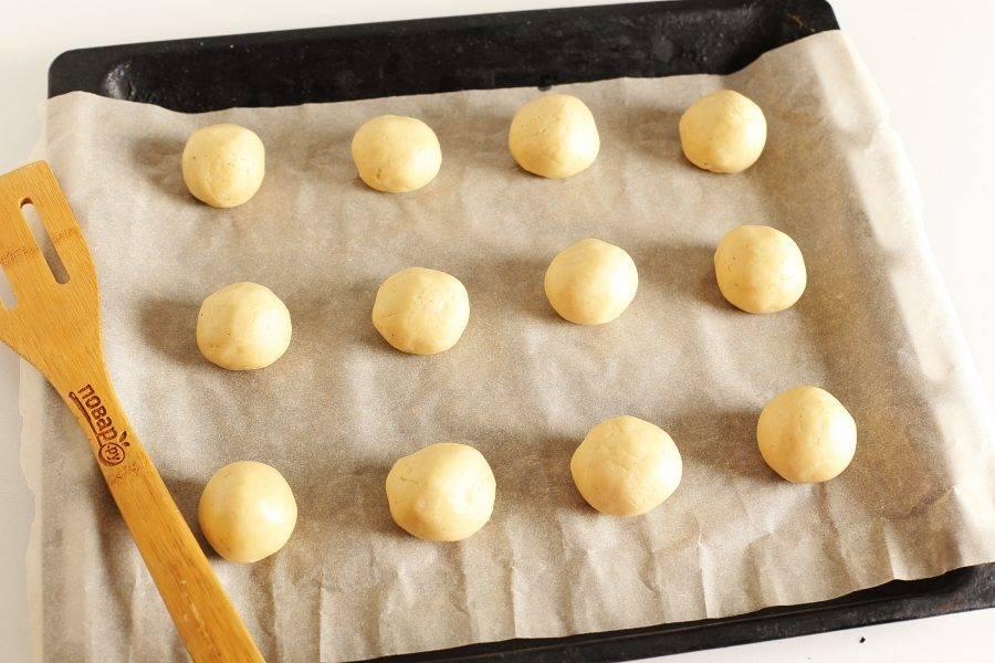 Когда будете готовы, просто отщипывайте маленькие кусочки теста, скатывайте шарики размером с грецкий орех и выкладывайте их на противень, застеленный пергаментом.