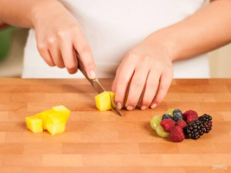 4.Мою ягоды, отправляю их в миску (виноград без косточек, нарезаю его на 2 части), мою и очищаю манго, нарезаю его небольшим кубиком.