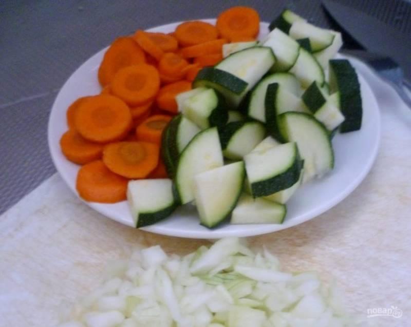 Нашинкуйте средними кусочками очищенный лук, довольно крупно нарежьте промытый цукини и кружками нарубите очищенную и промытую морковь.