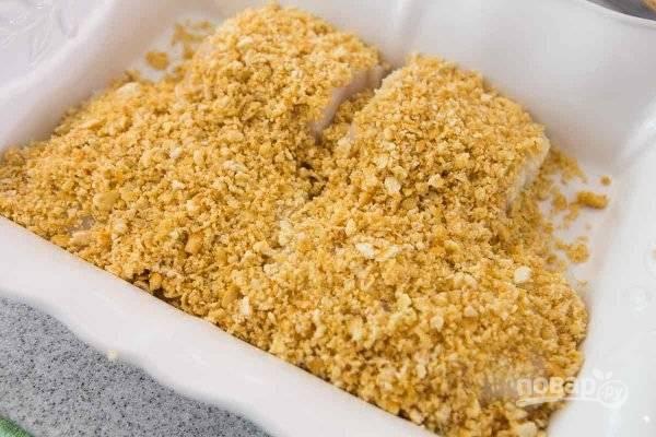 5.Растопите сливочное масло и смешайте с крошкой, выложите массу поверх рыбы, как бы укрыв ее.