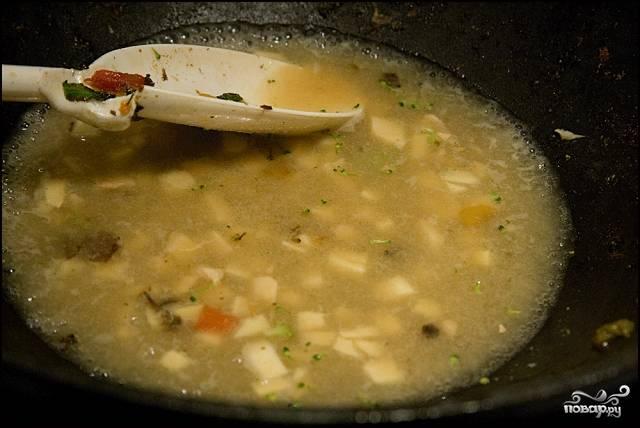В сковороду налейте бульон, забросьте в него измельченный имбирь, муку, чеснок, соль и перец, доведите пряную смесь до кипения.
