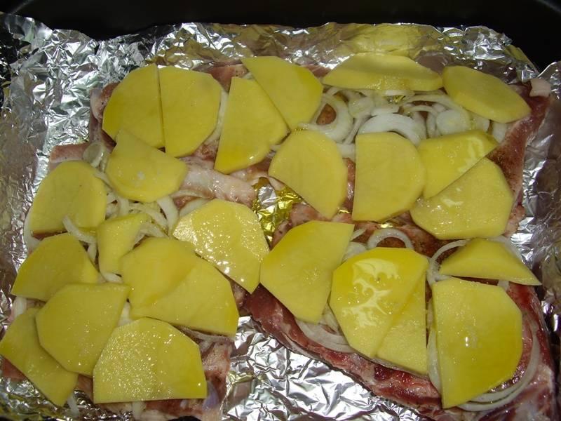 2. На противне расстилаем слой фольги, чуть смазываем ее маслом и выкладываем мясо. Наверх - картошку ломтиками и лук колечками. Картошку тоже немного солим. Запекаем, закрыв сверху фольгой, полчаса.