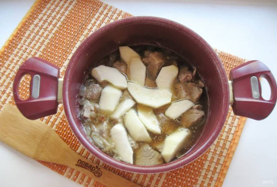 Дальше можно готовить такую свинину двумя способами. Налейте в кастрюлю воду (300 мл), добавьте еще две столовые ложки соевого соуса, соль и перец черный молотый по вкусу. Поставьте на плиту кастрюлю и готовьте мясо на самом минимальном огне до мягкости. Можно то же самое сделать в духовке. После одно большое яблоко помойте, очистите от кожуры, удалите семена и нарежьте дольками. Добавьте к мясу и тушите еще 10-15 минут.