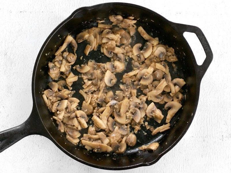 4.Верните сковороду на огонь, добавьте чеснок и обжаривайте его 1 минуту, затем выложите грибы, обжарьте их до испарения жидкости.