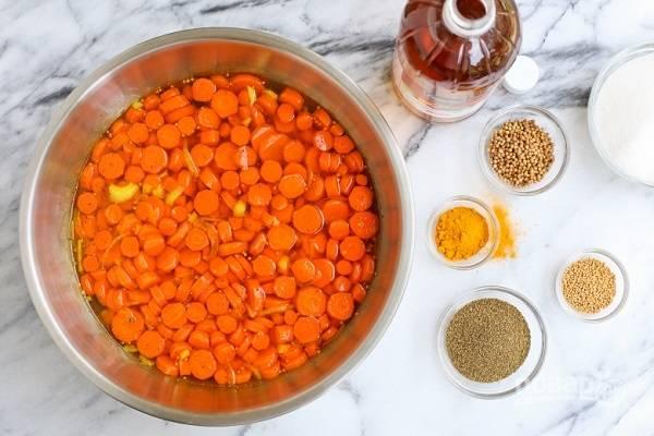 2. В отдельной кастрюле соедините сахар, воду, уксус, соль и специи. Поставьте на огонь, доведите до кипения и проварите минут 5, чтобы сахар хорошо растворился. Снимите с огня и аккуратно выложите морковь в горячий маринад.