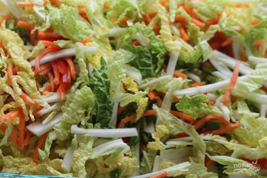 2.Нарежьте тонкими полосками сладкий красный перец, морковь и зеленый острый перец, выложите все овощи в большую миску и перемешайте.
