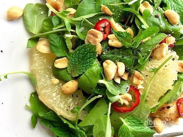 6. На тарелку для подачи выложите курицу, помело, листья салата. Полейте заправкой, добавьте орешки и листья мяты. Аккуратно перемешайте.