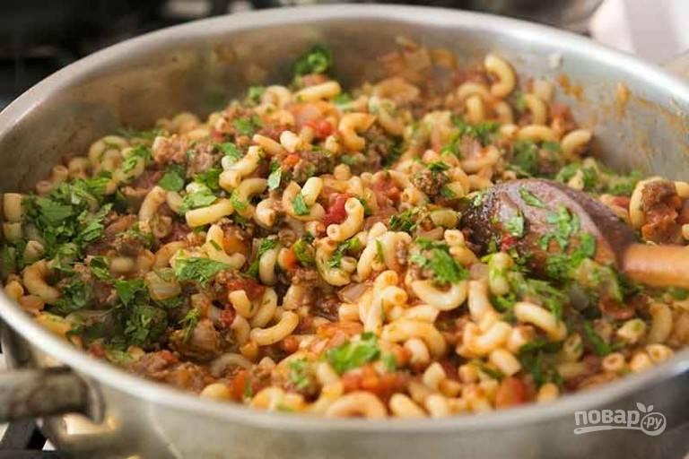 4.Выложите к соусу отваренные макароны, перемешайте, добавьте зелень и тушите все несколько минут.