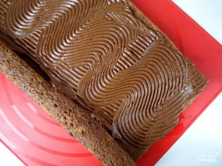 На готовый корж выложите шоколадную начинку, хорошенько ее разровняйте по всей поверхности бисквита. Заверните бисквит рулетом, оставьте его в холодильнике на пару часов, чтобы как следует пропитался.