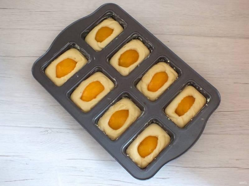 """Формочки для кексов смажьте обильно сливочным маслом. Разлейте тесто на 2/3 объема формочки. В серединку выложите персики и слегка """"утопите"""" в тесто. Поставьте выпекаться кексы в разогретую духовку до 200 градусов на 15-20 минут. Учитывайте особенности своей духовки."""