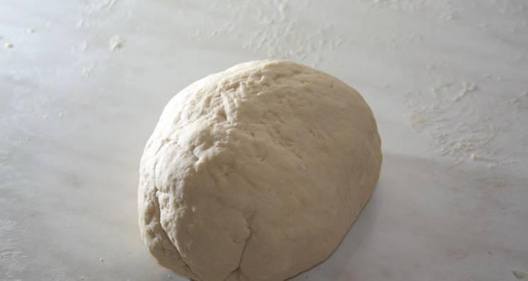 Приготовим тесто на пельмени. Просеиваем на стол муку, сделав по центру воронку. Мяту залейте кипятком и остудите. Теплую мятную водичку смешайте с яйцами и солью. Полученную смесь влейте в воронку, по часовой стрелке, аккуратно замесите тесто. Накройте тесто пленкой и оставьте в теплом месте на 30 минут.