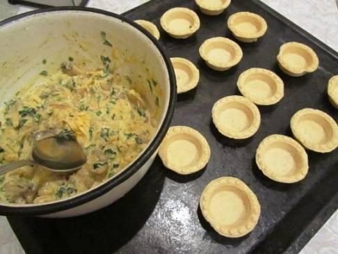 2. Ждем, пока грибы остынут. Теперь к этой смеси добавим майонез, зелень, яйцо, тертый сыр. Перемешаем, и этой массой наполняем тарталетки. Прогреваем духовку.