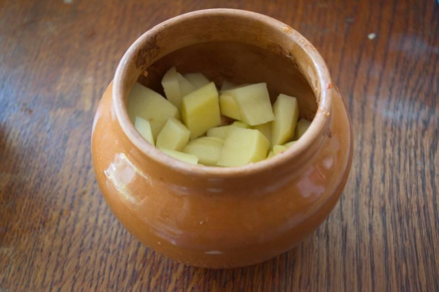 Картофель очистите. Нарежьте небольшими кусочками (большие долго будут пропекаться) и выложите поверх мяса.