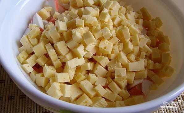 Сыр нарезаем мелкими кубиками. По моему мнению, если потереть его на терке, то он теряется в салате.
