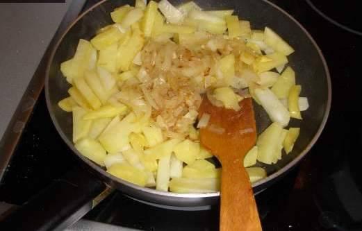 Затем к картошке добавляем обжаренный на отдельной сковородке лук и готовим на медленном огне, хорошо перемешав.
