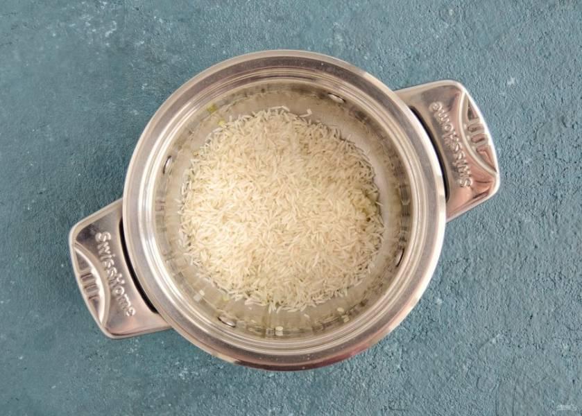 Добавьте рис и перемешайте, чтобы рис впитал в себя все масло и жидкость от лука и чеснока.