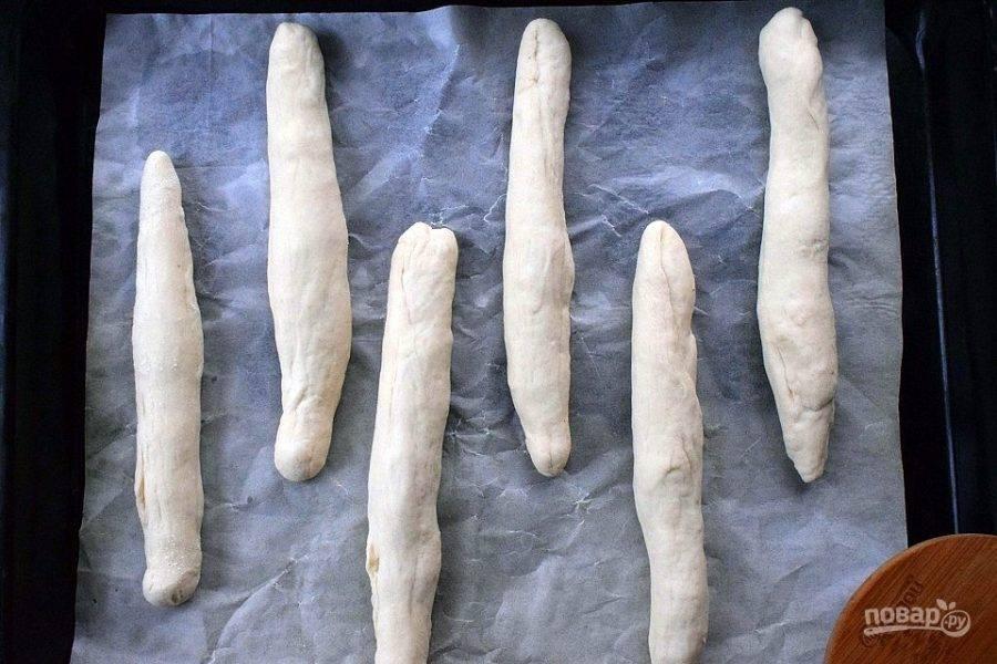Каждую часть скатайте в колбаску длиной примерно 18-20 см. Разместите заготовки на противень с пергаментом для выпечки на небольшом расстоянии друг от друга. Поставьте запекаться в разогретую до 220 °C на 15-20 минут, до золотистой корочки. Ориентируйтесь по своей духовке.