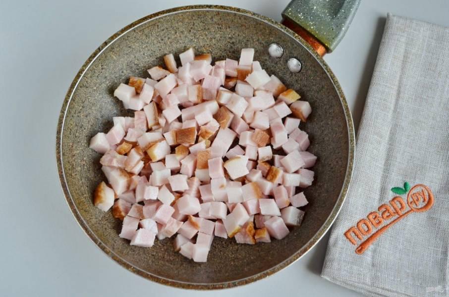 Теперь приготовьте начинку. Для этого порежьте бекон кубиками, на сухой сковороде жарьте до вытапливания жира (смальца).