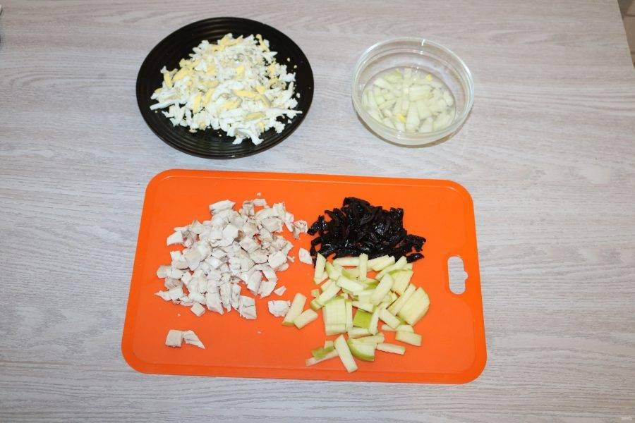 Куриные яйца очистите, верхушку одного белка оставьте для украшения. Яйца натрите на крупной тёрке. Куриную грудку нарежьте кубиками. Яблоко нарежьте соломкой, сбрызните слегка лимонным соком. Чернослив нарежьте соломкой. Лук нарежьте кубиками, замаринуйте в смеси уксуса и воды с добавлением щепотки сахара.