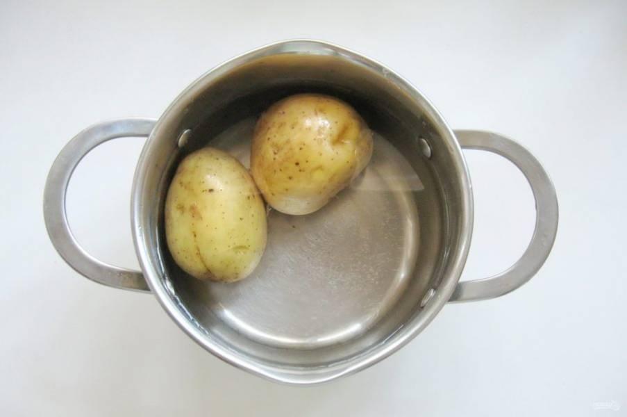 Картофель помойте и выложите в кастрюлю. Залейте водой, варите до готовности. После охладите.