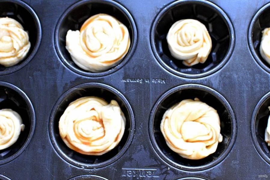 Уложите розаны в смазанные формочки. Формочки должны быть качественные либо силиконовые, чтобы облегчить вынимание готовых булочек.