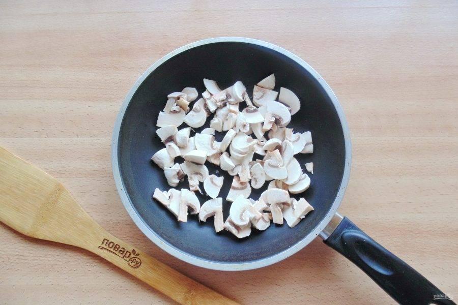 Шампиньоны очистите, помойте и нарежьте не очень мелко. Выложите в сковороду с подсолнечным маслом и поджарьте.