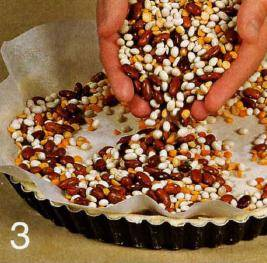 Разогреть духовку до 190 С. Круглую форму для выпечки смазать маслом. Раскатать тесто в тонкий круглый пласт и выложить его в форму так, чтобы были закрыты дно и бока формы. Наколоть тесто в нескольких местах вилкой, накрыть бумагой для выпечки, сверху насыпать сухую фасоль. Поставить в духовку и выпекать 15- 20 мин.