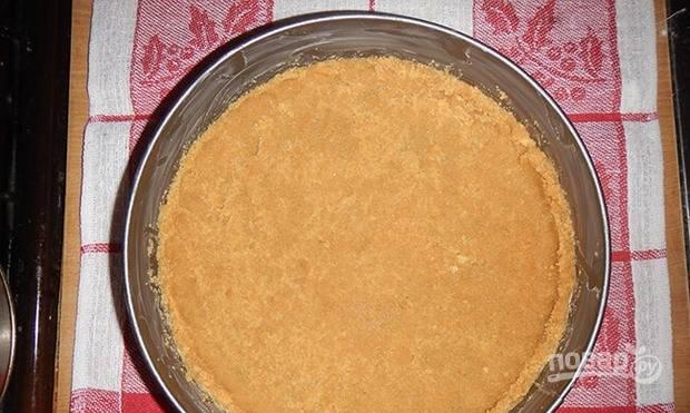 Растопите сливочное масло на водяной бане и влейте его к песочной крошке. Замесите тесто, выложите его в форму для запекания и распределите так, чтобы получился корж с бортиками. Выпекайте корж в духовке, разогретой до 180 градусов, пятнадцать минут.