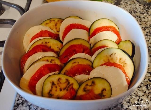 Выложите в форму по очереди кружочки баклажанов, помидоров и моцареллы. Но не слоями, а скорее в ряд, как на фото.