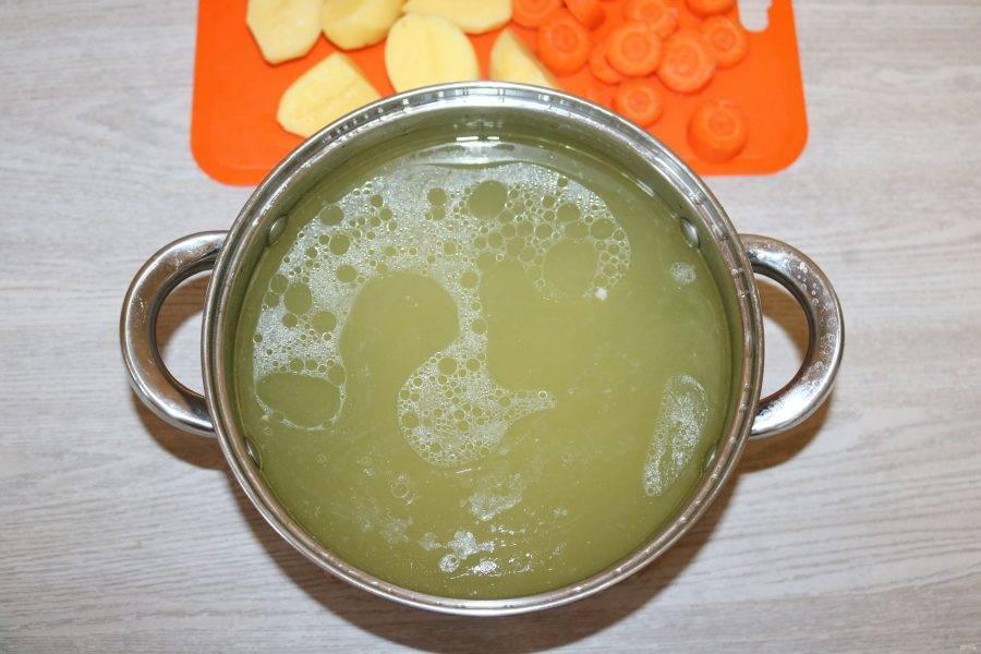 Извлеките курицу из бульона. В кипящий бульон добавьте нарезанный картофель и морковь.