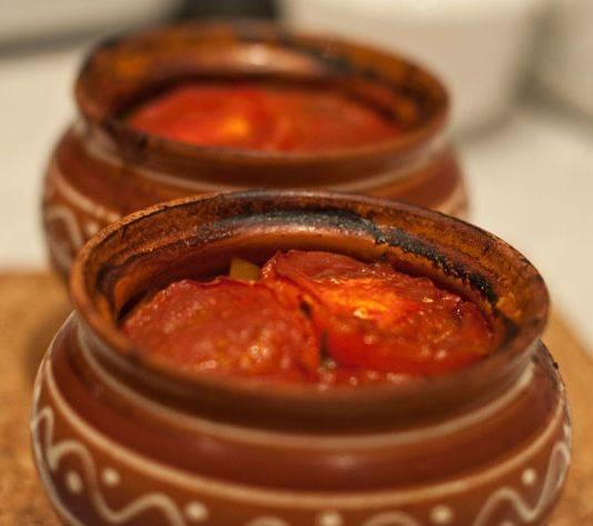 Добавляем в каждый горшочек пару капель табаско и заливаем все томатным соком так, чтобы он почти полностью накрывал помидоры, но не доходил до краев горшочка (иначе будет брызгать). Ставим горшочки в духовку (холодную) и включаем температуру 200 градусов, запекаем мясо с картофелем и овощами час. По прошествии времени убавляем температуру до 150 градусов, снимаем с горшочков крышки и готовим все еще 30 минут.