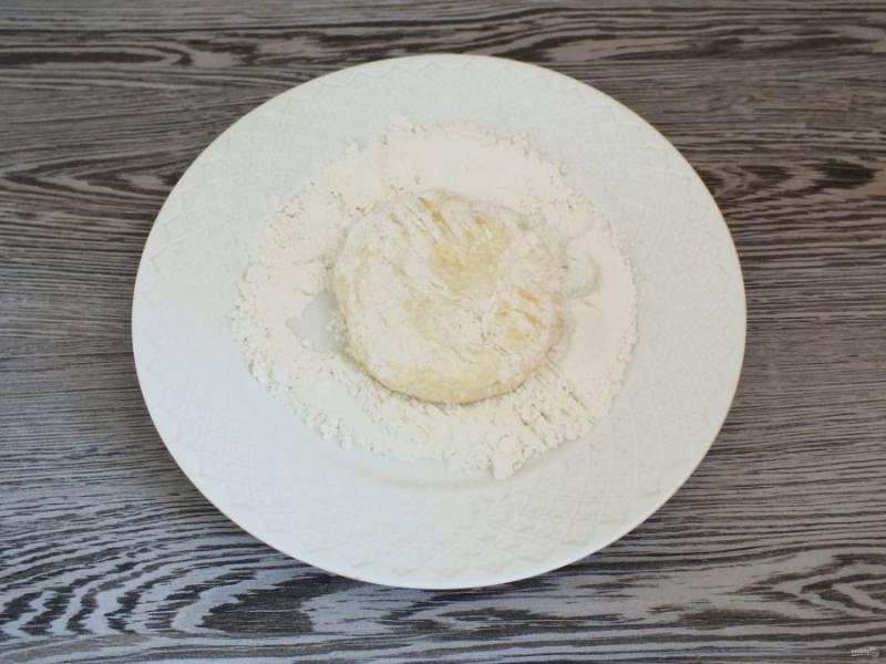 В тарелку насыпьте муку. Творожно-картофельную массу поделите на равные части, скатайте в шарик, придайте форму творожника. Обваляйте в муке с двух сторон.
