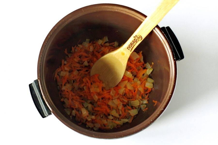 "Лук нарежьте кубиками, морковь натрите на терке. Налейте в чашу мультиварки масло и обжарьте овощи на режиме ""Жарка"" до мягкости."