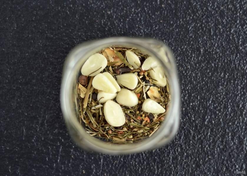 На дно стерилизованных банок выложите нарезанный пластинами чеснок и специи.
