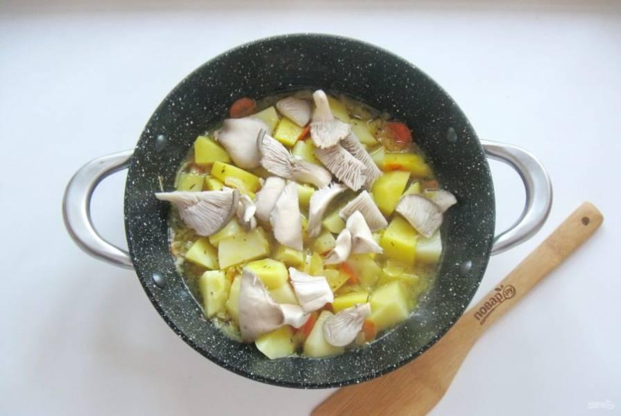 Сковороду накройте крышкой и тушите картофель 20 минут. После добавьте нарезанные грибы.