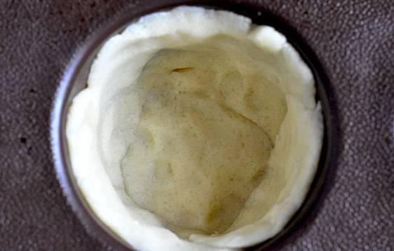 Скатываем тесто в шар, отщипываем от него кусочки и формируем в форме для выпечки бортики. Ставим формочки в морозилку на 15 минут.