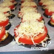 Далее баклажаны выложить на смазанную маслом противень. Далее необходимо выкладывать на баклажаны слоями продукты - сначала первый слой тертого сыра, затем помидор и сверху снова слой тертого сыра.
