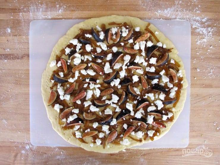 Фиги вымойте и нарежьте дольками, распределите на тесто лук, покрошите сыр, выложите фиги. Переместите пиццу на противень и выпекайте в разогретой духовке при 180 градусах, пока она не станет богатого золотистого цвета.