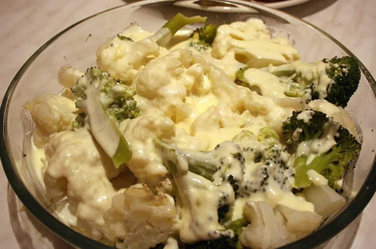 Складываем овощи в форму для запекания и заливаем их молочным соусом. Сливочный сыр трем на крупной терке, присыпаем им овощи. Запекаем блюдо в духовке до золотистой корочки. Температура 220 градусов.