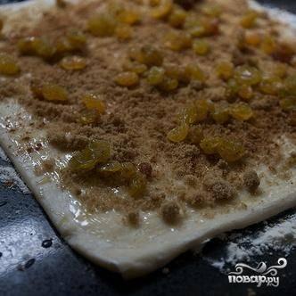 2. Слегка посыпать мукой деревянную доску или рабочую поверхность. Выложить на доску лист размороженного слоеного теста. Смазать весь лист растопленным, а затем охлажденным сливочным маслом. Посыпать тесто коричневым сахаром, молотой корицей и изюмом, оставляя нетронутыми границы по краям на 2,5 см.