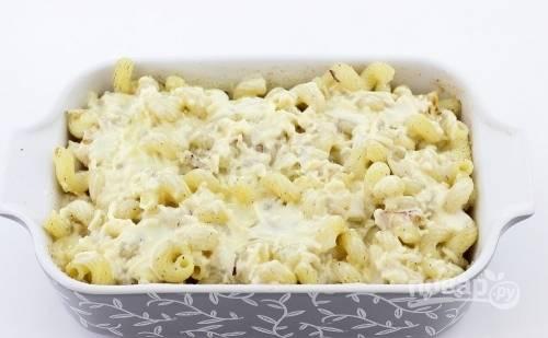 Жаропрочную форму смажьте маслом и присыпьте сухарями. Выложите в неё макароны с грудкой. Сверху влейте заливку.