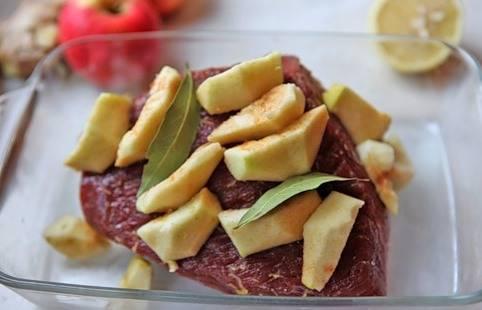 Выкладываем мясо в форму для запекания, а на него кладем очищенные от сердцевины и кожуры дольки яблоки и лавровый лист.