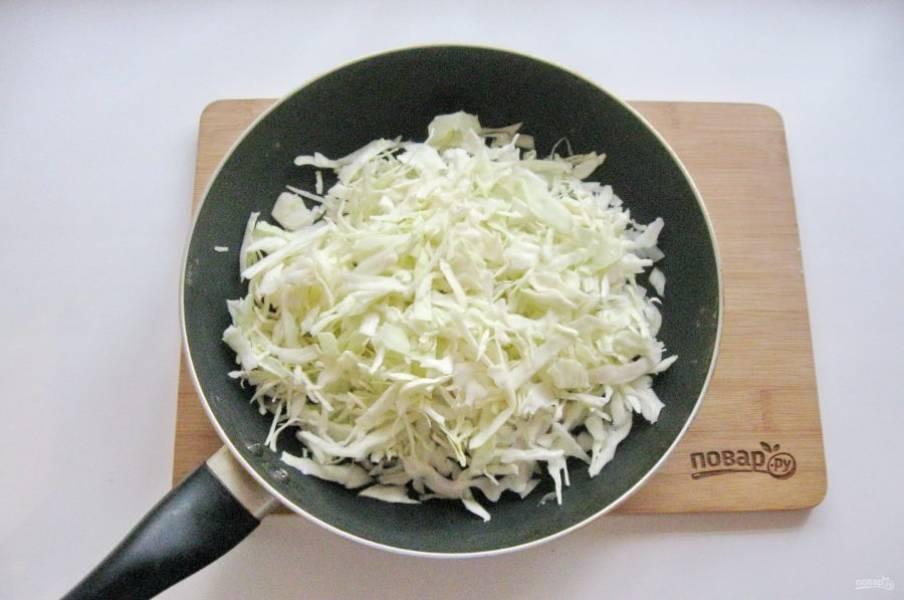 Пока тесто подходит, приготовьте начинку для пирожков. Капусту нашинкуйте соломкой и выложите в сковороду. Налейте подсолнечное масло и 2-3 столовые ложки воды.