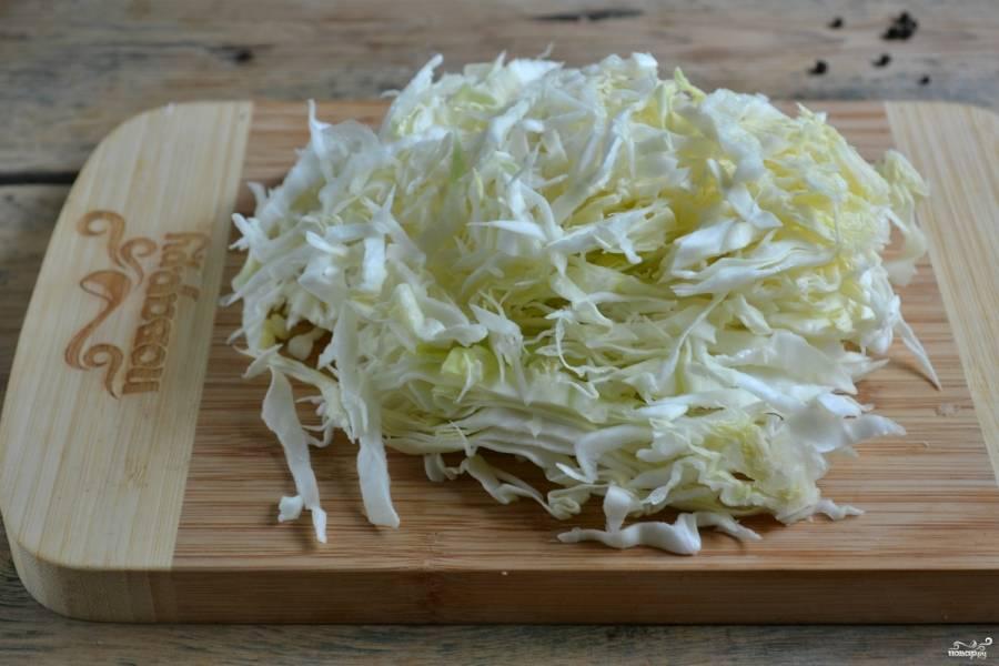 Полкочана капусты нашинкуйте на специальной тёрке или измельчите ножом.