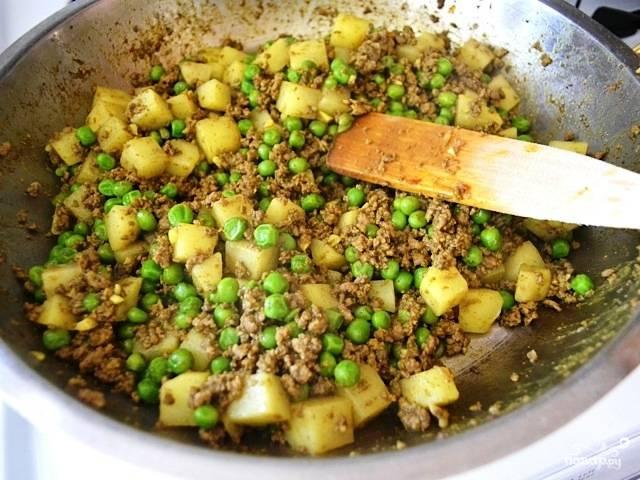 Как только картофель станет мягким, добавляем в блюдо горошек. Перемешиваем и готовим до готовности всех ингредиентов. Регулируем на соль и снимаем с огня.