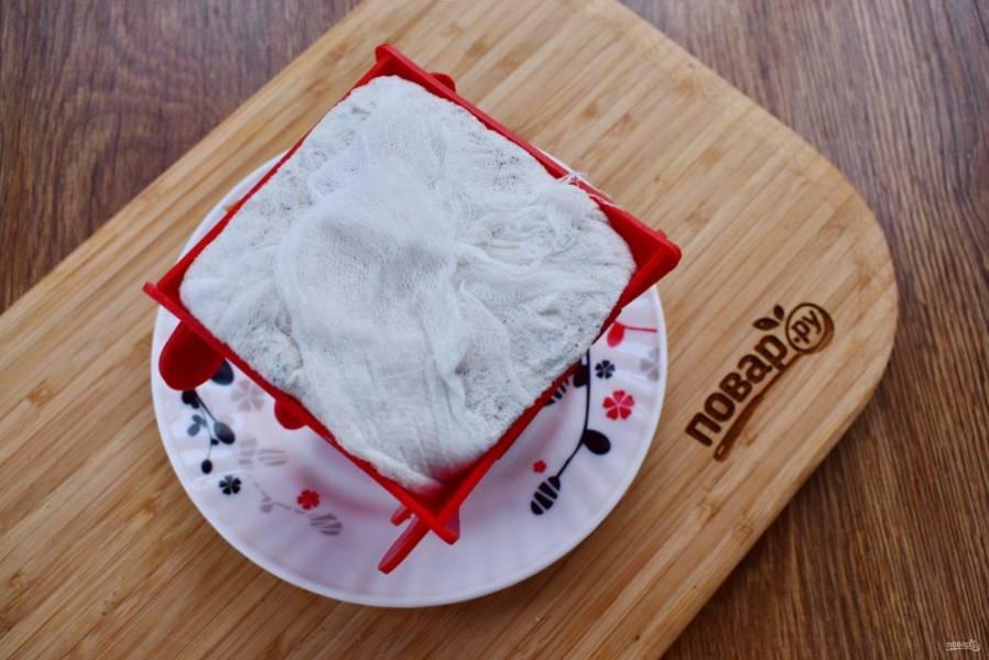 Форму для пасхи намочите и поставьте в глубокую тарелку. В форму постелите марлю, сложенную в два слоя. В творожную массу добавьте тертый шоколад, перемешайте.